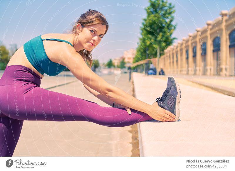 Attraktive Frau mit schönen blauen Augen, die ihr Bein streckt, während sie an einem Sommermorgen in einem Stadtpark glücklich aussieht. strecken Fitness