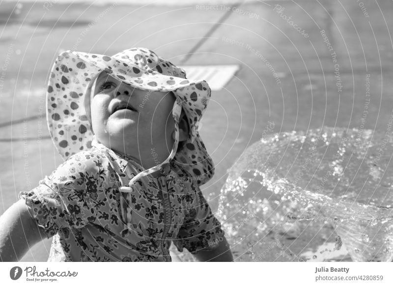 Ein Jahr altes Baby in einem Wasserpark an einem heißen Tag; Kleinkind trägt Sonnenschutz UPF Sonnenhut und Badeanzug, wie sie schaut zu den Eltern für Beruhigung