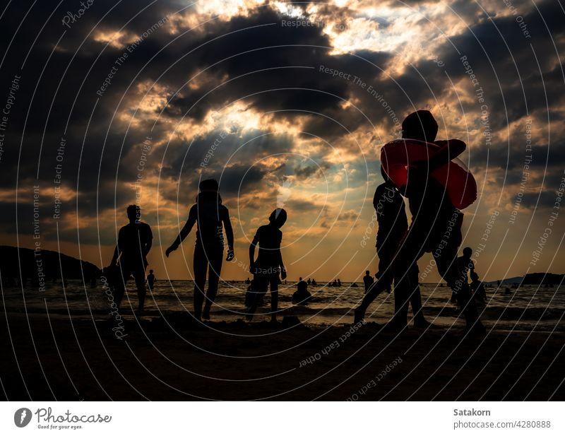 Silhouetten von Menschen spielen im Meer an einem öffentlichen Strand Landschaft Himmel Sand Abend Urlaub MEER Sonne Sonnenuntergang Zusammensein Sommer jung