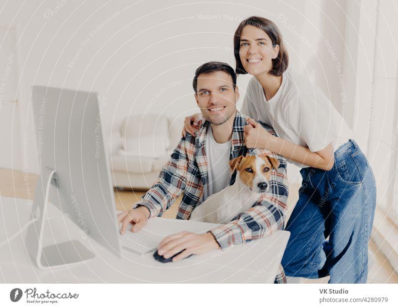 Bild der glücklichen brunette lächelnde Frau lehnt an den Schultern Ehemänner, die Tastaturen auf Computer, im Internet surfen und suchen neue Wohnung auf der Website zu kaufen, posieren in geräumigen Zimmer mit Haushund