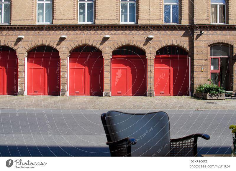 Sitzplatz vor dem Feuerwehrhaus Sessellehne Backsteinfassade Bogen Garagentor Ausfahrt Bürgersteig Symmetrie Architektur Einfahrt Prenzlauer Berg Berlin Stil