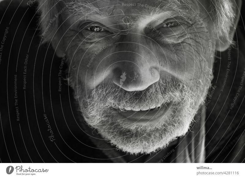 Lebenserfahrung Porträt Mann Blickkontakt Blick in die Kamera direkt Erzähler kommunizieren erzählen sprechen verschmitzt lächeln Bart Vollbart weißhaarig