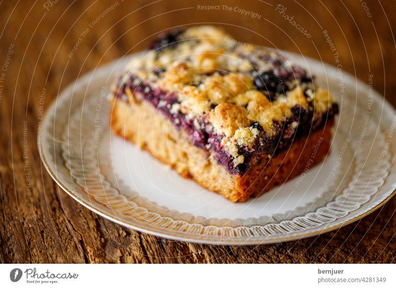 Heidelbeerkuchen auf dunklem Holz Blaubeerkuchen Kuchen süß Heidelbeere Beere lecker gesund Nahaufnahme Dessert Essen vegan Rohform Vegetarisch Scheibe