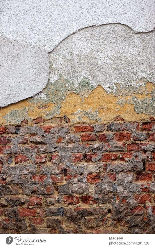 Bröckelnder Putz und und freigelegtes altes Mauerwerk aus rotem Backstein eines Altbau in Wettenberg Krofdorf-Gleiberg bei Gießen in Hessen Wand Fassade