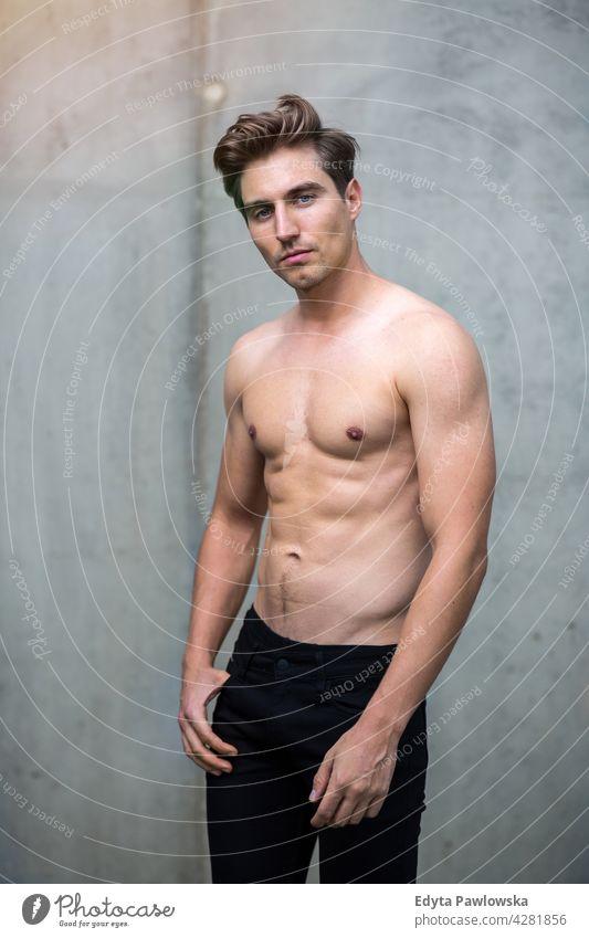 Hübscher junger Mann vor grauer Wand Menschen Person Typ modisch ernst sexy passen schlank Körper Behaarung Stil Stehen eine stylisch Kaukasier Junge Ausdruck