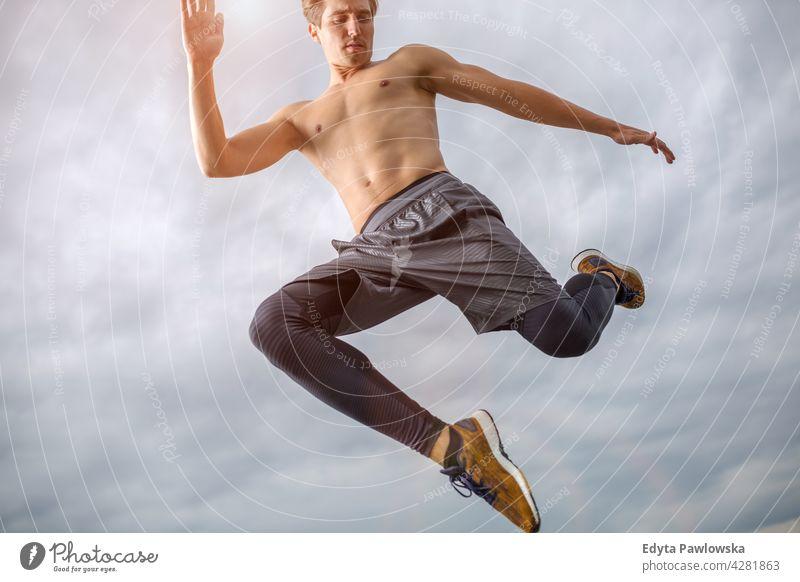 Mann springt gegen den Himmel Menschen Person Typ modisch ernst sexy passen schlank Körper Behaarung Stil Stehen eine stylisch Kaukasier Junge Ausdruck Männer