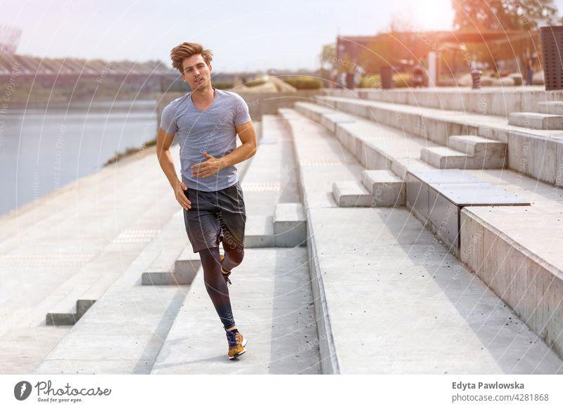 Junger Mann läuft in städtischem Gebiet Jogger Läufer Joggen rennen Menschen jung männlich Energie Übung Bekleidung trainiert. Fitness Erholung Sport