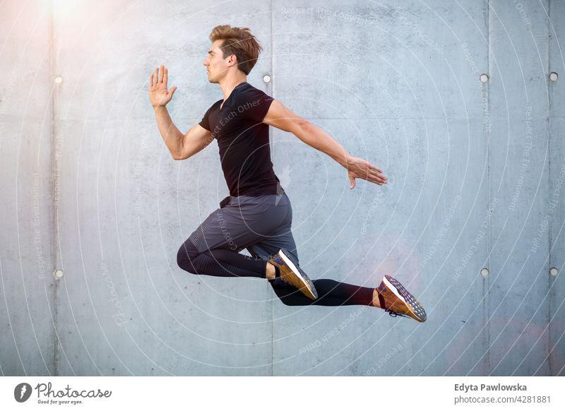 Hübscher junger Mann springt gegen graue Wand Menschen Person Typ modisch ernst sexy passen schlank Körper Behaarung Stil Stehen eine stylisch Kaukasier Junge
