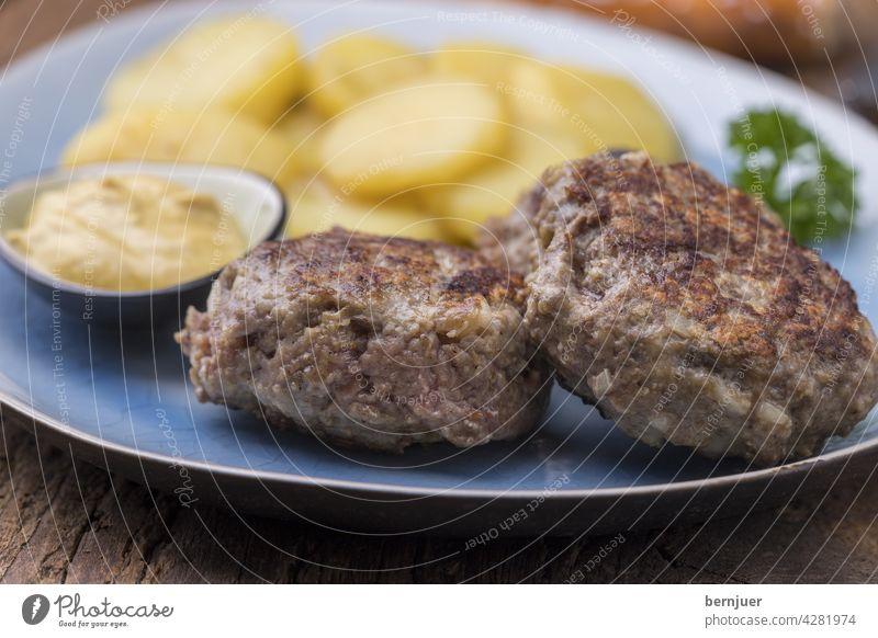 bayerische Fleischplanzerl mit Kartoffelsalat Holz Bier Essen Küche hausgemacht Teller Breze Brezel pflanzerl Rindfleisch deftig geröstet gebacken gegrillt