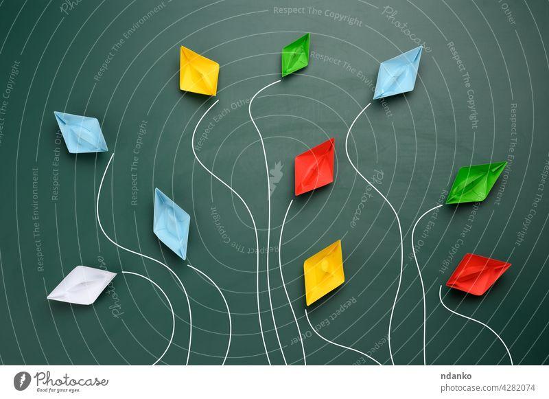 eine Gruppe von mehrfarbigen Papierbooten fliegt in verschiedene Richtungen auf grünem Hintergrund Boot blau Chef Business Konkurrenz Konzept kreativ