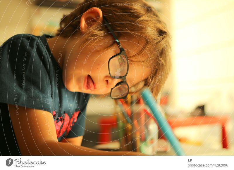 Kind trägt Brille und schreibt, während es sehr konzentriert ist Oberkörper Porträt Muster talentiert zeichnen Zeichenutensilien Abenteuer Lebensfreude Freude