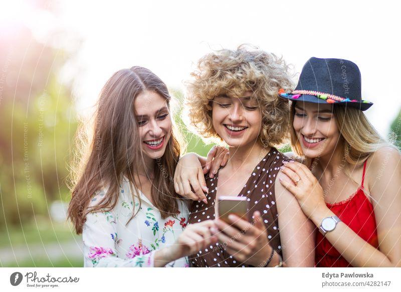 Glückliche junge Frauen haben Spaß mit Smartphone Sonnenuntergang Sommer Menschengruppe Zusammensein lässig schön attraktiv Mädchen drei Personen Freunde