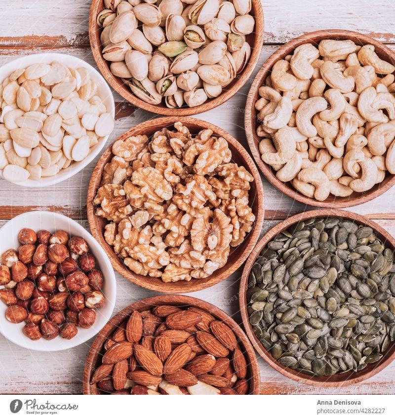 Verschiedene Arten von Nüssen in Holzschalen Nut Schalen & Schüsseln Sortiment Walnussholz Auswahl Snack Haselnuss mischen Gesundheit Samen Pistazie Kürbiskerne