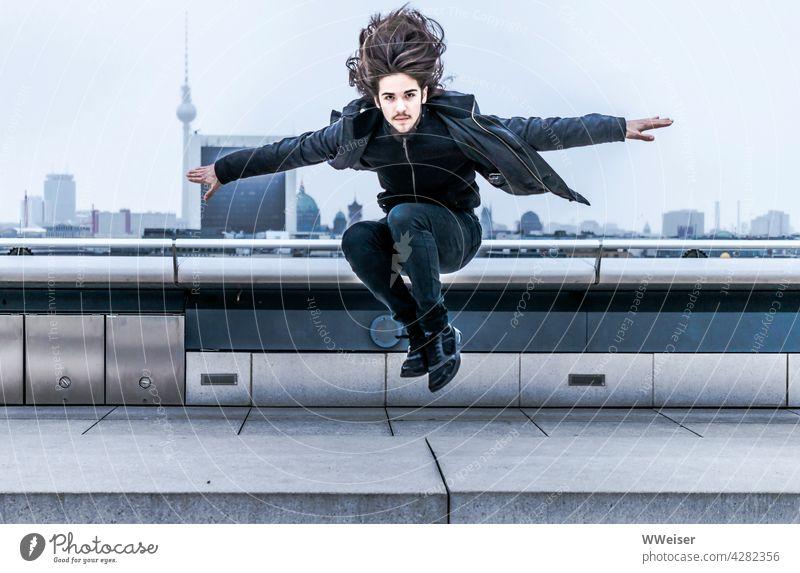 Der dynamische junge Mann mit den langen Haaren landet auf dem Dach einer Großstadt springen energisch schwungvoll oben Reichstag Parkour Panorama mutig