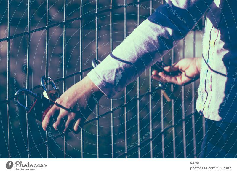 Liebesschlösser, Zaun, Kinderhände Außenaufnahme Farbfoto Stadt Fröhlichkeit träumen Liebesbekundung Liebesgruß Liebeserklärung Freundschaft Liebesschloss