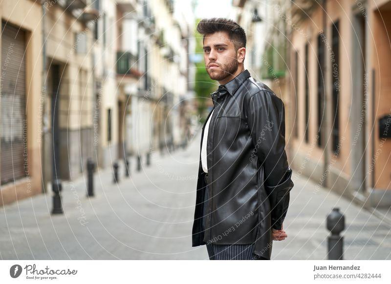 kaukasischer Mann mit Bart, bekleidet mit schwarzer Lederjacke jung Kaukasier Vollbart angekleidet Jacke Typ professionell Model stylisch modisch gutaussehend