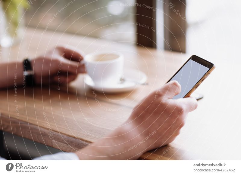 Geschäftsmann Hand hält ein Telefon mit isolierten Bildschirm gegen moke up und trinken Kaffee im Coffee Shop verschwommen Kaffeetasse Hintergrund, Mock up Konzept