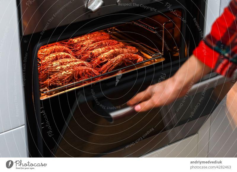 gegrillte garnelen und gebratene garnelen in der heimischen küche. frau hält einen garnelengrill auf einem rostfreien Tablett und kocht in einem elektroofen, um eine nachtparty zu feiern. meeresfrüchte