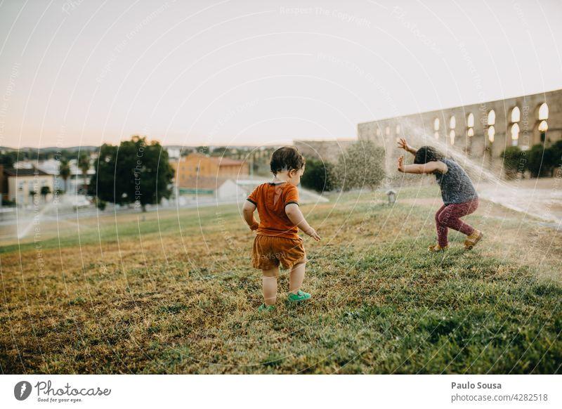 Bruder und Schwester spielen mit Wassersprinklern Geschwister Kind Sommer Erfrischung Außenaufnahme Spielen Mensch Freude Farbfoto Kindheit Junge Mädchen