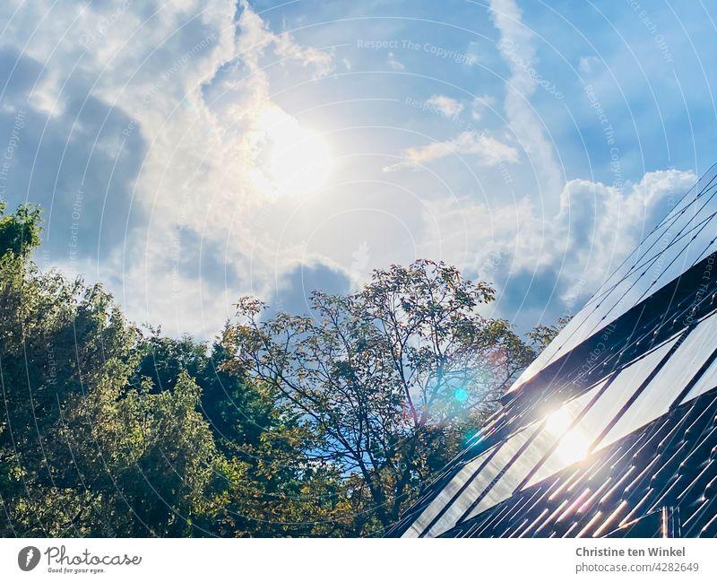 Die Sonne scheint hell vom leicht bewölkten Himmel und spiegelt sich in den Kollektoren der Solaranlage und der Photovoltaikanlage eines Wohnhauses Solarthermie