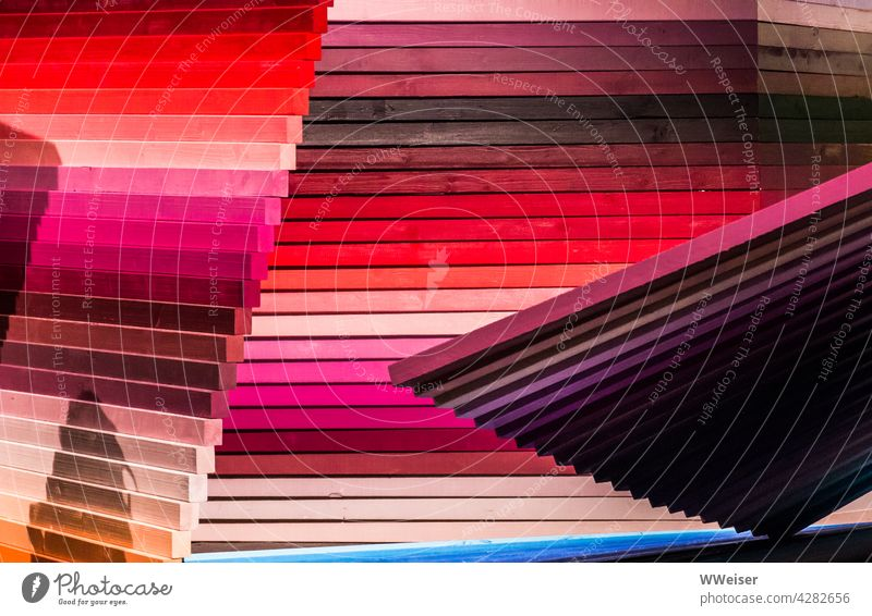 Ein kunstvolles Arrangement aus fächerartig zusammengeklebten Holzlatten in Rottönen Latte Latten Holzbrett Bretter Wand kreativ gestreift Streifen aneinander