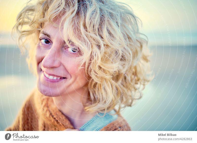 Junge reife blonde kaukasische Frau Porträt im Freien in einem Strand. Lifestyle Wellness Frauen Gesundheit Erholung Fröhlichkeit entspannend