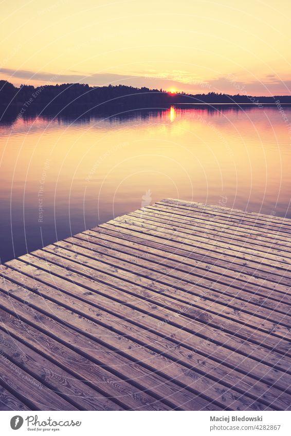 Holzsteg bei goldenem Sonnenuntergang, selektiver Fokus, Farbtonung angewendet, Strzelce Krajenskie, Polen. See Pier im Freien Natur Reflexion & Spiegelung