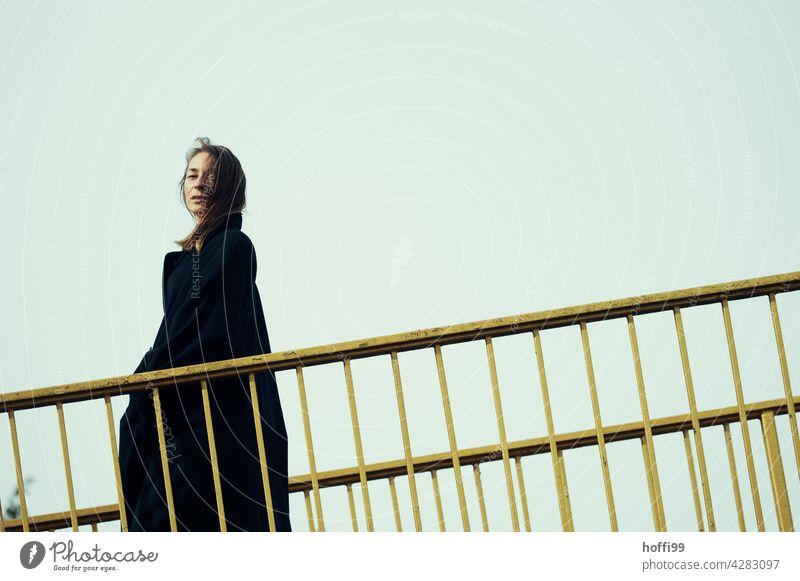 die junge Frau geht über eine Brücke und blickt selbstbewusst in die Kamera Junge Frau elegant Lifestyle feminin Mode langhaarig 18-30 Jahre Haare & Frisuren