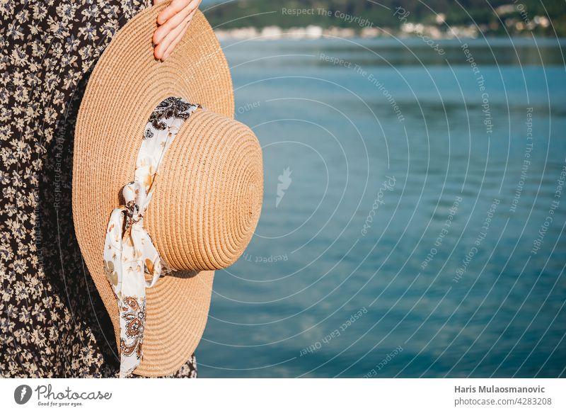 Sommerhut in der Hand in der Nähe des Meeres mit copyspace Bad Strand schön Schönheit blau Küste Textfreiraum Mode Frau Mädchen Hut Feiertag freudig Freizeit