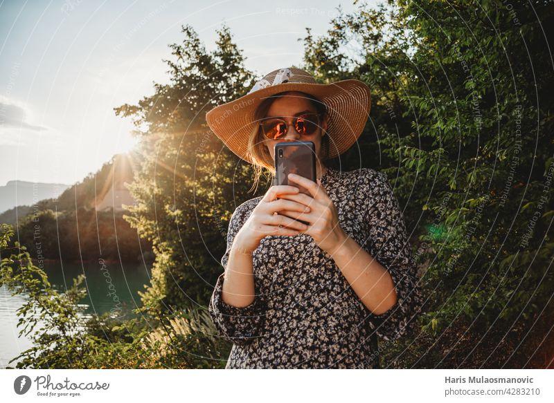 Frau mit Hut und Sonnenbrille mit Handy im Sonnenuntergang auf der Seeseite 5g Erwachsener App attraktiv Hintergrund schön Schönheit Kaukasier Mitteilung