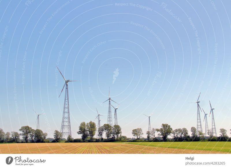 viele Gittermast-Windkraftanlagen stehen in der Landschaft vor blauem Himmel Windrad Stromerzeugung Energie Energiegewinnung erneuerbare Energie CO2 Natur Feld