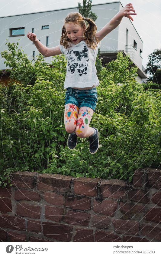 Mädchen springt von Mauer Blumen Blumen auf Beine gemalt Blumen malen Kindheit Kindheitserinnerung spass Spielen Bewegung Energie Freude sprung springen bunt