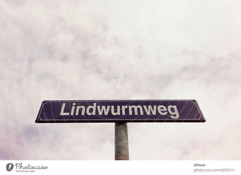 """lila Straßennamensschild mit weißer Schrift """" Lindwurmweg """" vor bewölktem Himmel / Orientierung Straßenschild Straßennamenschild drachenartiges Fabelwesen"""
