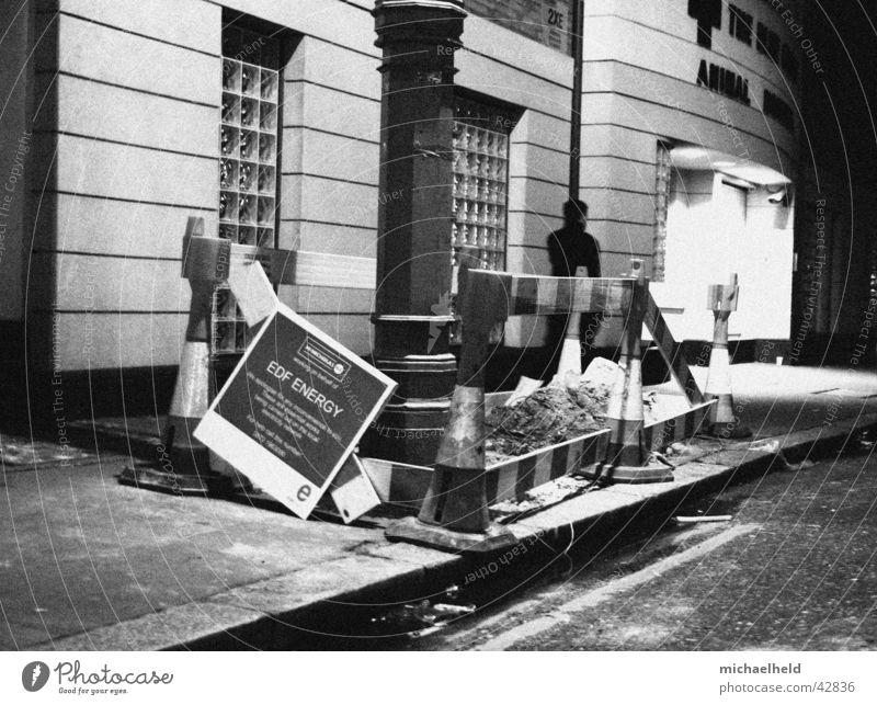 Lonely at night Baustelle gehen Nacht London schwarz weiß Bürgersteig Lampe Laterne Barriere Mantel dunkel Mensch Schilder & Markierungen Licht Schwarzweißfoto