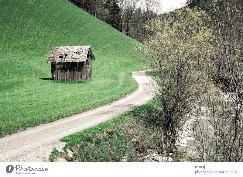 Häuschen im Grünen, mit eigener Zufahrt und Bach. Einsamer Heustadl auf einer Wiese neben einem Feldweg. Hütte Farbfoto alt Kontrast Natur Heuschober Haus