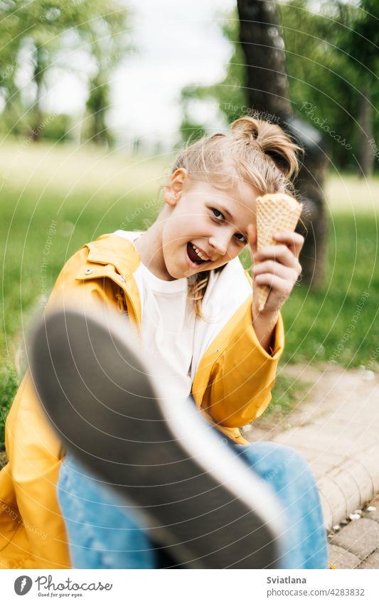 Porträt eines lustigen blonden Teenager-Mädchens mit Eis bei einem Spaziergang im Park. Kind im Freien Sommer Speiseeis gelb Stilrichtung Spaß Glück niedlich