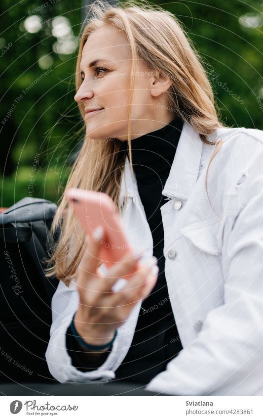 Glückliche Blondine sitzt auf einer Bank in einem Stadtpark, telefoniert und schreibt SMS mit Freunden Park Frau Lifestyle jung Menschen Mobile Mitteilung
