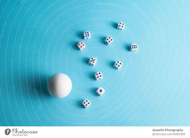 Minimales Layout mit einem weißen Ei und Würfeln auf blauem Hintergrund Spieleinsatz Tischplatte Menschengruppe Konzept Minimalismus Leben Arme Wette Geburt