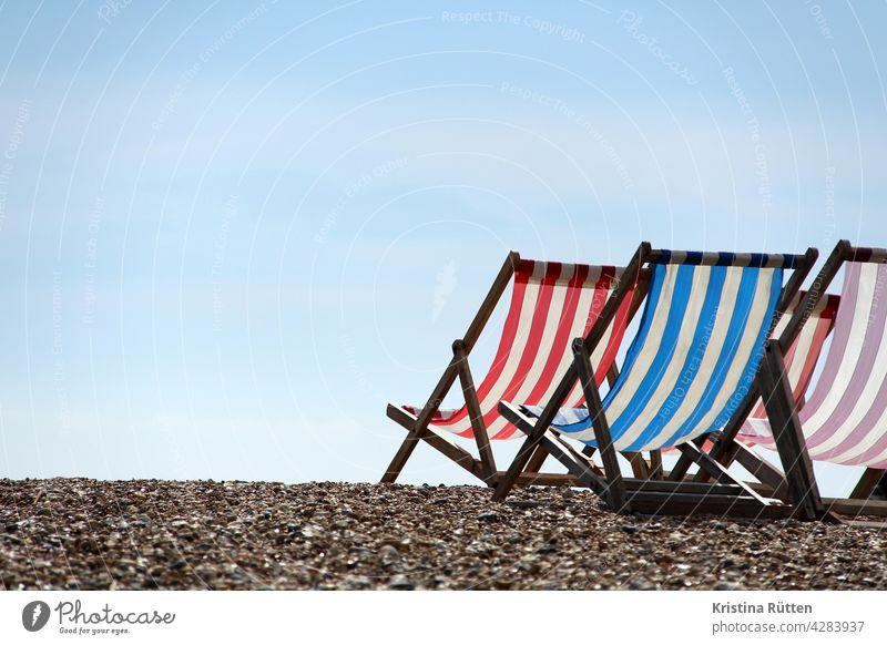gestreifte liegestühle am strand, dem himmel zugewandt klappstühle deckchairs kiesstrand streifen sommer sonne sonnig urlaub ferien erholung entspannung auszeit