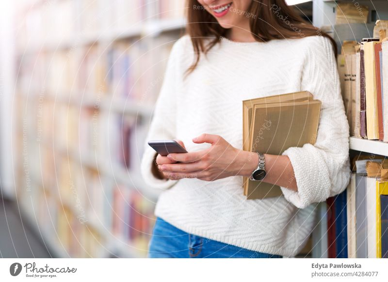 Junge Studentin in einer Universitätsbibliothek genießend Lifestyle jung Erwachsener Menschen eine Person lässig Kaukasier positiv Glück Lächeln Frau attraktiv