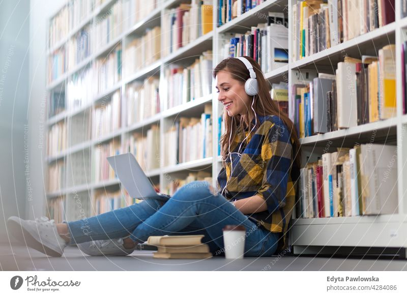 Weibliche College-Studentin sitzt in einer Bibliothek und benutzt einen Laptop genießend Lifestyle jung Erwachsener Menschen eine Person lässig Kaukasier