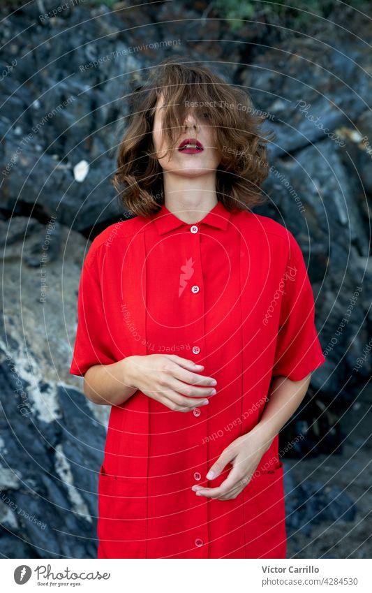 Eine elegante modische frische schöne Frau in einem roten Vintage-Kleid mit Felsen Hintergrund. Porträt Schönheit jung Mode Model Behaarung Gesicht Person