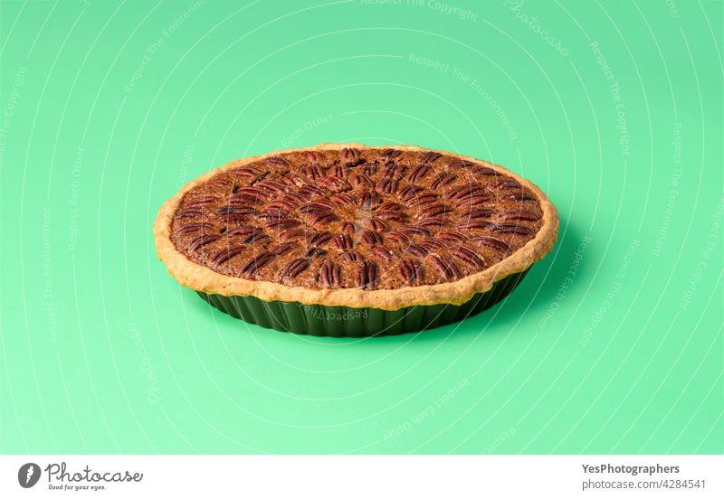 Pecan-Kuchen auf einem grünen Tisch. Ganzer Kuchen isoliert auf einem farbigen Hintergrund. oben Amerikaner Herbst gebacken Bäckerei braun Tabelle Weihnachten