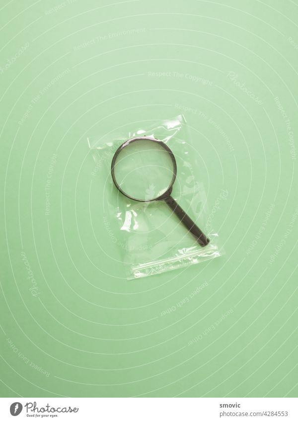 Lupe in Plastiktüte verpackt. Zubehör Tasche konzeptionell konvex vergrößern Glas Beteiligung Instrument Linse Minimalismus Objekt Paket Kunststoff Wissenschaft