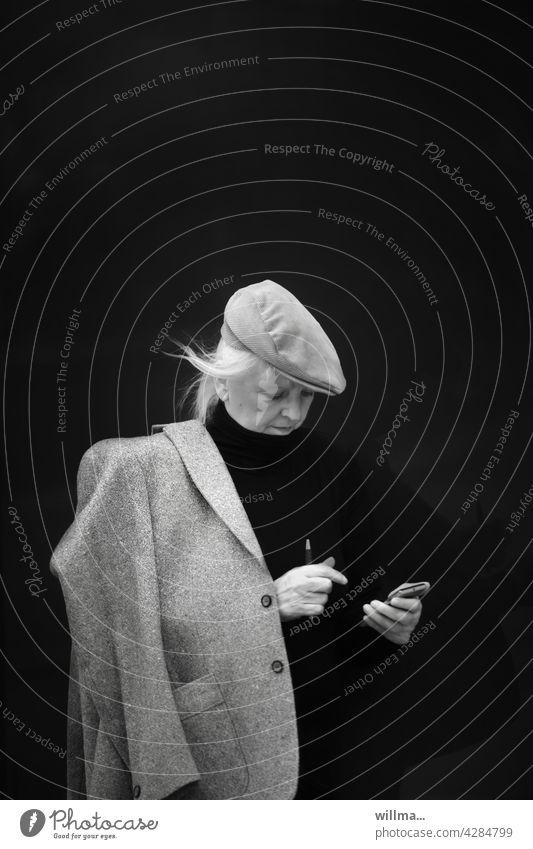 moderne Kommunikation  per Wisch und Weg Frau Sakko Schiebermütze Smartphone IPhone Handy Mobile Nachricht lesen Whatsapp Kurznachricht SMS Internet Email