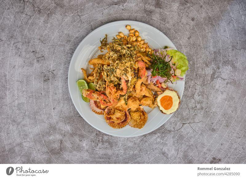 Peruanisches Essen: Jalea de pescado oder Fischkrapfen mit gebratenem Maniok und Zwiebelsalat mit Chili, serviert auf einem weißen Teller. Gebratene Meeresfrüchte