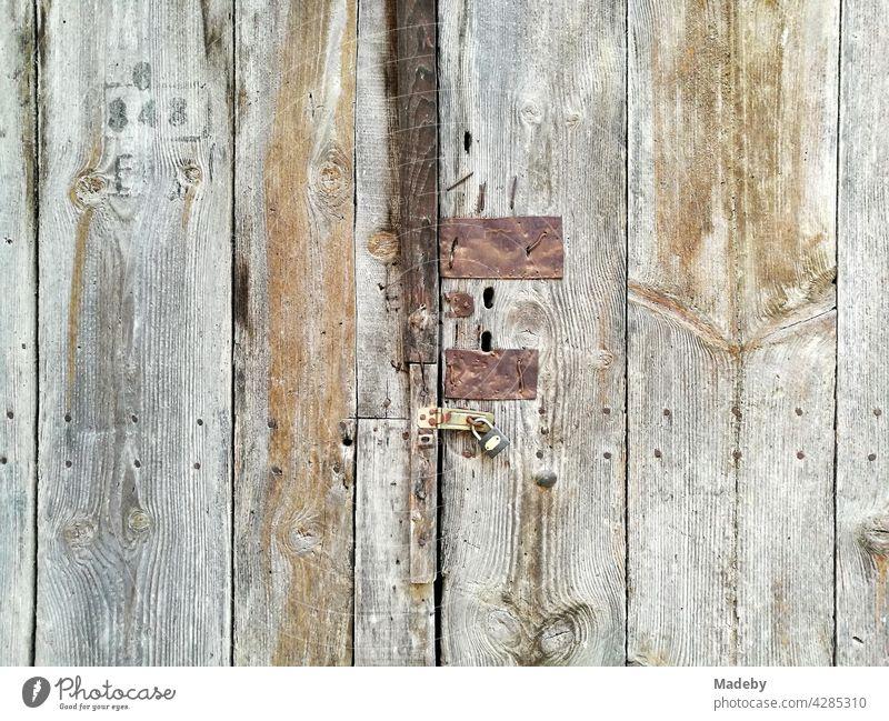 Alte Holztür mit rostigen Beschlägen und Spuren aus vergangenen Zeiten in der Altstadt von Tarakli in der Provinz Sakarya in der Türkei Bretter Verschlag