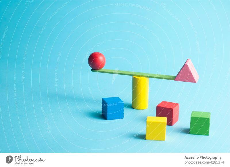 Minimalistisches Konzept mit einer Stabschwingerskala und bunten geometrischen Figuren Gleichgewicht minimalistisch Zusammensetzung 3d Würfel Einblick