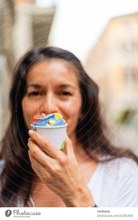 hispanische Frau hält einen Becher mit regenbogenfarbenem Eis Eiscreme Hand Essen frisch Straßenessen Menschen smartwatch Hände Frucht Beteiligung lgbt Farben