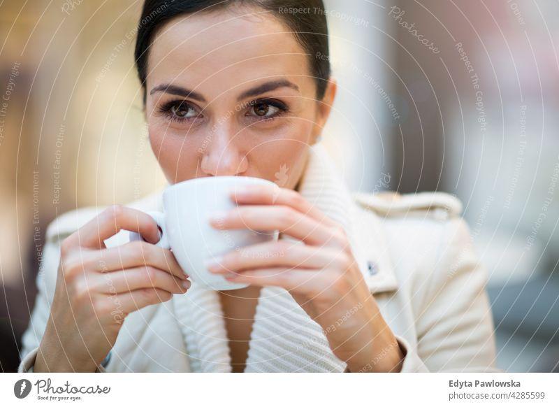 junge Frau trinkt Kaffee im Café trinken Getränk genießend Lifestyle Erwachsener Menschen eine Person lässig Kaukasier positiv sorgenfrei Sitzen Glück Lächeln
